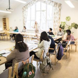 ett stort klassrum med ungdomar. I mitten står läraren. Internationell kurs, språkkurs.