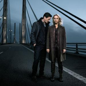 Karaktärerna Henrik och Saga står på en bro i mörkret.