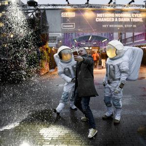 En man tar en selfie med två astronauter vid Helsingfors mässcentrum.
