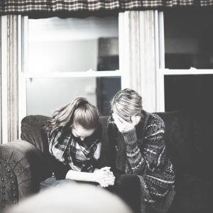 Två kvinnor sitter i en soffa och håller huvudet i händerna