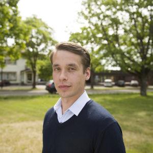 En man iklädd en ljusblå skjorta och en mörkblå tröja. Han är utomhus. I bakgrunden skymtar kommunhuset i Ingå.