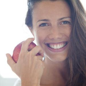 Leende kvinna håller ett äpple.