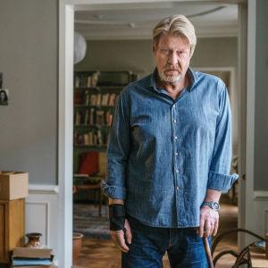 LMJ står med sin käpp i sin bostad.