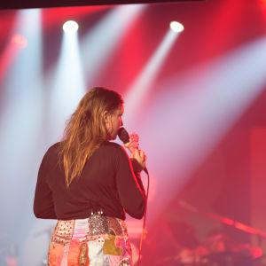 Linnea Henriksson på scenen. Ryggen mot publiken.