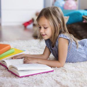 tyttö lukee kirjaa lattialla maaten