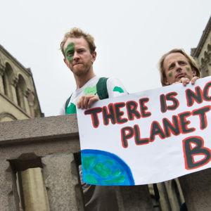 """kaksi miestä pitää kylttiä jossa lukee englanniksi """"ei ole olemassa planeetta b:tä"""""""