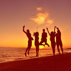 Yötöntä yötä juhlivia ihmisiä rannalla