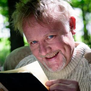 Sagofarbrorn Mårten Holm läser en bok i skogen.