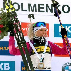 Glad Mari Laukkanen höjer skidor och blombukett i luften.