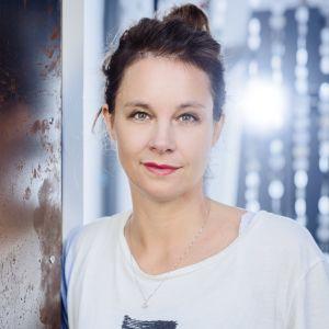Sara Stridsberg står vid en vägg