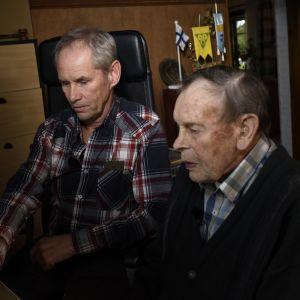 två män sitter koncentrerade