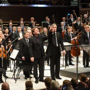 Säveltäjä Magnus Lindberg, kapellimestari Hannu Lintu ja RSO kiittävät yleisöä Tempus fugit -teoksen kantaesityksen jälkeen.