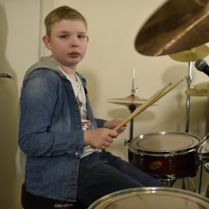 liten pojke spelar trummor