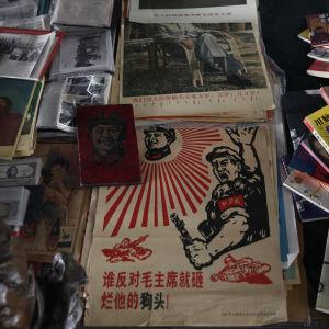 Gamla föremål från kommunisttiden säljs på en loppmarknad i Peking. Texten på affischen säger att alla som motsätter sig Mao Zedong ska krossas.