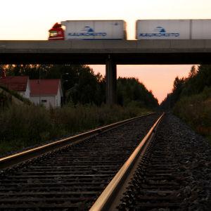 En långtradare susar förbi på en järnvägsbro.