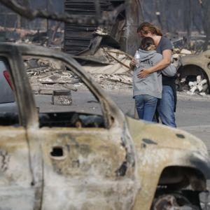 Två överlevande kramas vid ruinerna efter sitt hem i Santa Rosa, Kalifornien 10.10.2017