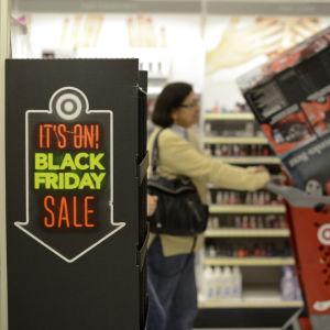 """En kvinna som är ute och julhandlar under shoppingdagen """"Black Friday""""."""