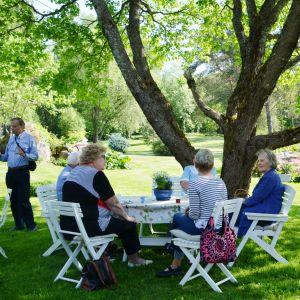En grupp kvinnor sitter under ett träd i en trädgård.