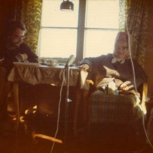 Ikkunan edessä,  pöydän ääressä istuu nuori partainen mies ja  kaksi vanhempaa huivipäistä naista nojatuoleissa. Naisten huivien alla on hatunkaltainen tötterö.