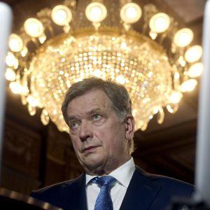 Sauli Niinistö under en kristallkrona.