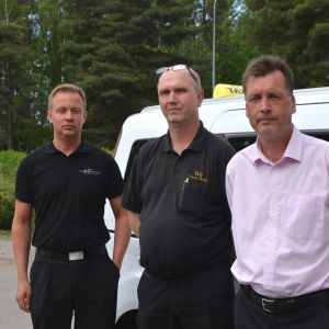 Tre män på rad framför taxibil utomhus.
