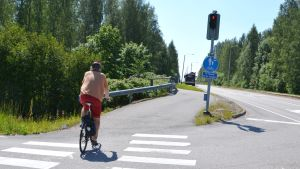 En man cyklar mot rött.