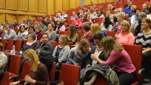 Människor sitter i ett auditorium.