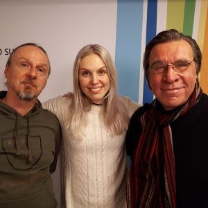 Juha-Pekka Sillanpää, Anne Lainto ja Harri Saksala seisomassa Radio Suomen tunnuksen edessä