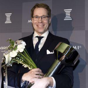 Olli Ohtonen med pokal och blomma på idrottsgalan
