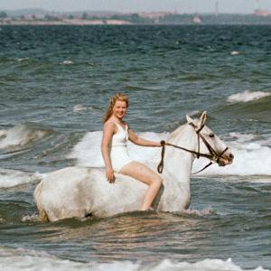 Nainen valkean ratsun selässä meren aalloissa. Kuva elokuvasta Muuttolintu (Opfergang)