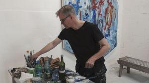 Taidemaalari Mikko Sakala ateljeessaan Taidekeskus Antareksessa Sippolassa maalipurkkien äärellä, taustalla hänen sini-puna-sävyinen teoksensa.