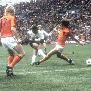 Tysk skjuter boll mellan holländskt försvar 1974