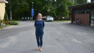Kvinna står på en parkeringsplats.
