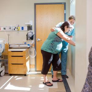 Barnmorska tar hand om gravid kvinna på sjukhus.