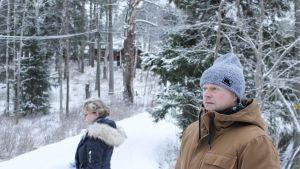nicke står och funderar på en snöig väg, i bakgrunden syns anna-maija nordling och idyllisk vintermiljö