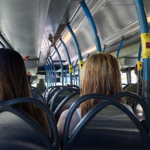 Ihmisiä bussissa.