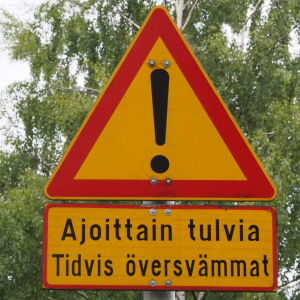 Liikennemerkki varoittaa ajoittaisista tulvista
