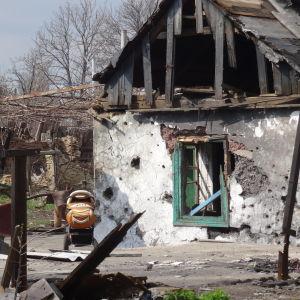 Ett sönderbombat hus, på gården plåt och trävirke men också en orange barnvagn