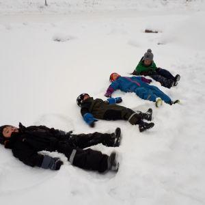 Barn leker i snön.