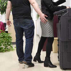 En man har sin hand på en kvinnas rumpa. De står i ett kontorslandskap vid en printer.
