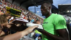 Usain Bolt delar ut autografer efter segerloppet.