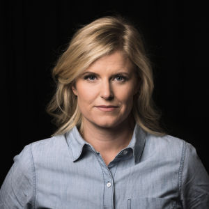 Ljushårig kvinna i grå skjorta framför mörk bakgrund