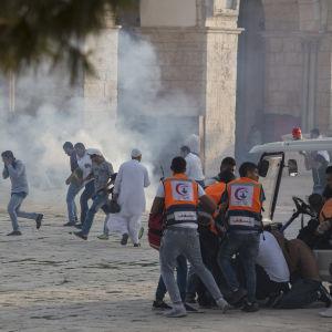 Personer omgivna av rök ocg damm springer iväg för att söka skydd under oroligheterna vid al-Aqsamoskén i Jerusalem den 27.7.2017.