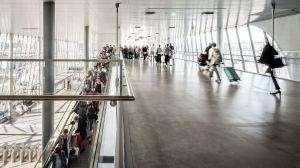 Passagerare med resväskor köar i en rulltrappa framför stora fönster.