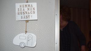 """En skylt hänger på en husvagnsdörr där det står """"Hemma bra men husvagn bäst""""."""