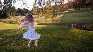 Flicka som springer på gräsmatta i sommarljus.