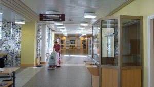 En städare tvättar golvet med en maskin vid ingången på Mjölbolsta sjukhusfastighet i Karis.