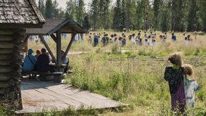 Niittykahvilassa istuvia ihmisiä (ei tunnistettavissaI, taustalla Hiljainen kansa -teoksen hahmoja.
