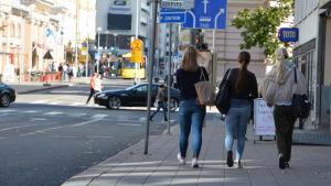 Ryggtavlan av tre unga kvinnor i Åbo centrum.