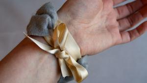 Ett armband av grått filttyg och ljusgult sidenband knutet med en rosett kring en handled.